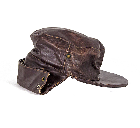 Leather cap with adjustable flap around the back of the head to be worn while riding a motorcycle
