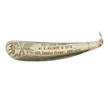 Metal shoe horn engraved with advertisement for H. Grundy & Co's and imagery of shoes and boots.