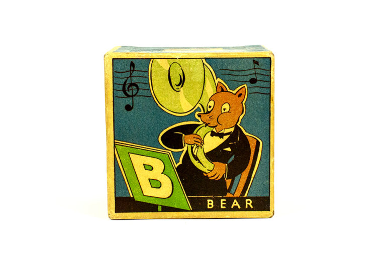 Each block is square and has illustrated decorations. There is one block for each note of the musical scale, C D E F G A B C. The blocks are hollow and have bells inside. The B block has an illustration of a bear playing a tuba and the sides have illustrations of the musical scale.