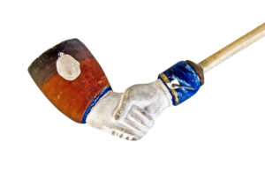 Clay pipe shaped and painted to look like two hands shaking.
