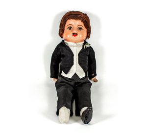 Doll with short brown hair and moustache wearing black suit with fake flower in buttonhole