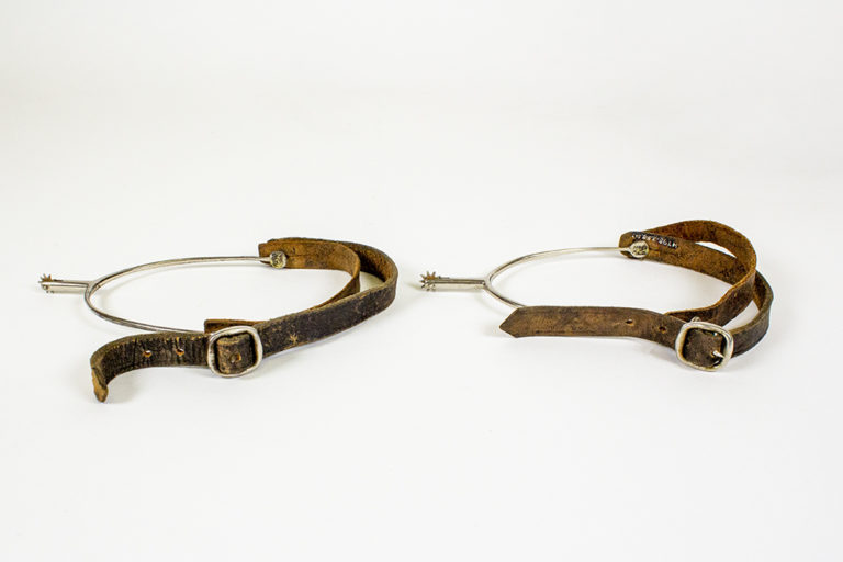 A pair of metal horse-riding spurs with leather adjustable straps
