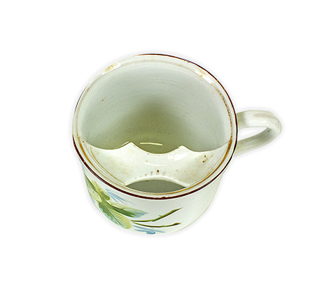 Tea cup with a red rim and floral design. Inside the cup, near the rim, sits a strip of porcelain to protect the moustache from getting wet while drinking