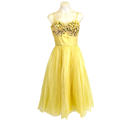 A knee-length bright yellow dress with shoulder straps, fabric detailing on the top, and a flair skirt