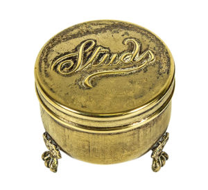 A metal contain with several small feet elevating it off the surface with the word 'Studs' written in cursive on the metal lid